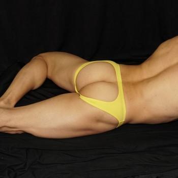 slip sin trasero color amarillo parecido a los jockstraps que tanto gustan para mostrar culo. Vista de espalda acostado