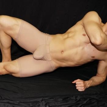 Calza corta que destaca el culo y el paquete masculino, color desnudo vista acostado de frente